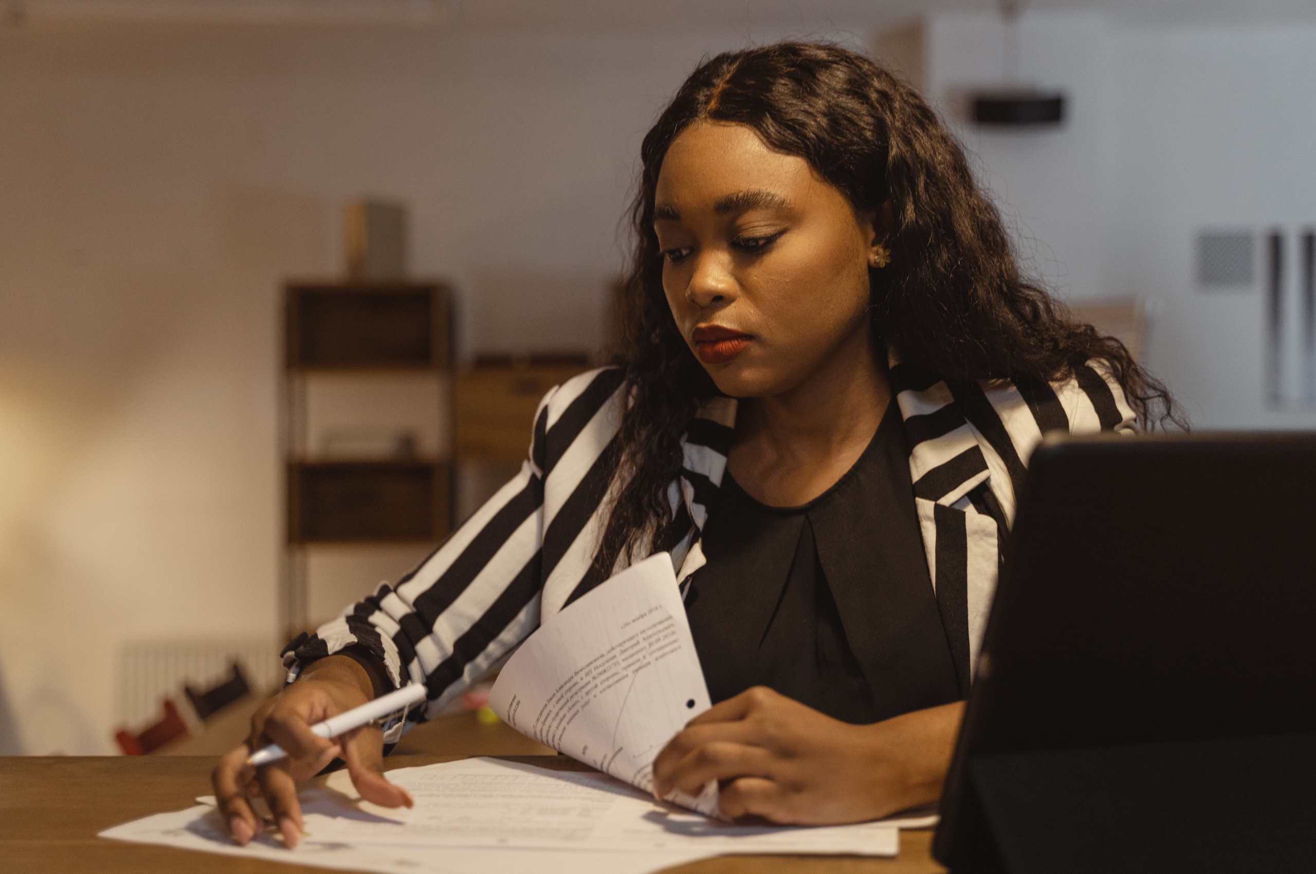 A Black woman sits in front of a laptop. She is turned to the side where she has papers on her desk that she seems to be writing on.