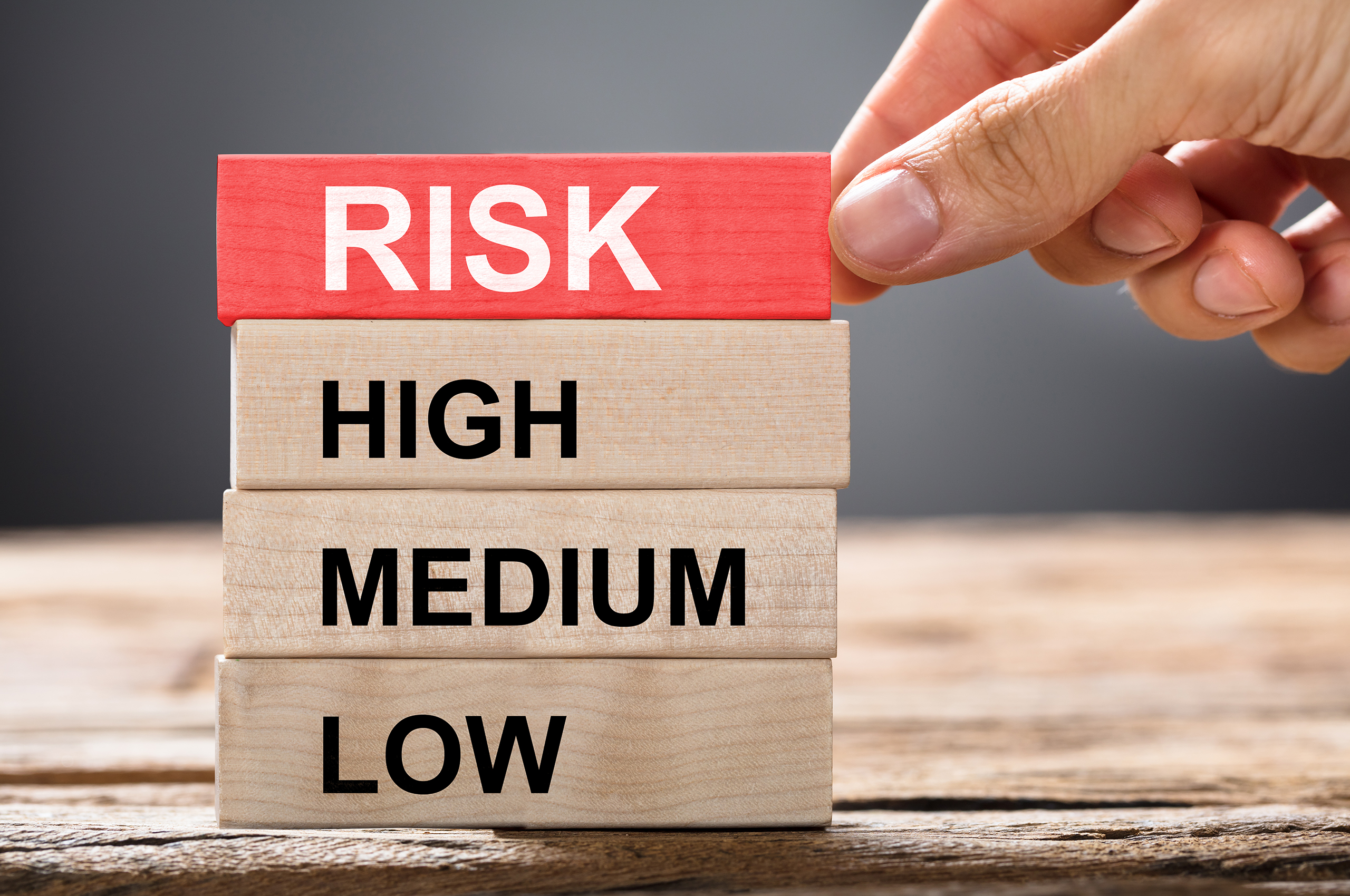 """A hand stacks wooden blocks. The blocks each have a word on them, and the top block is colored red. The top block reads """"risk"""", the others read """"high"""", """"medium"""", """"low."""" from top to bottom."""